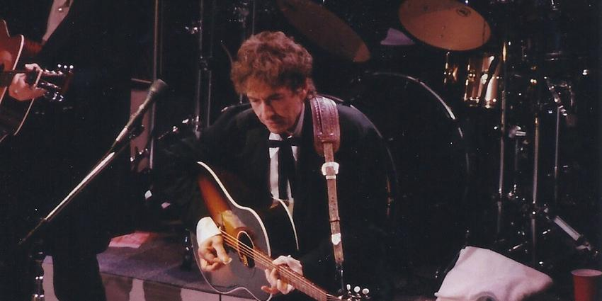 Bob Dylan performs, playing guitar and singing on stage, at the Bryce Jordan Center in 2011.