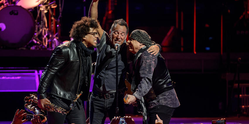 Bruce Springsteen & the E Street Band sing into a shared microphone during their concert at the BJC in 2016.