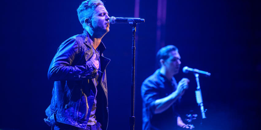One Republic sings together on stage under blue lights during their concert at the Bryce Jordan Center in 2013.