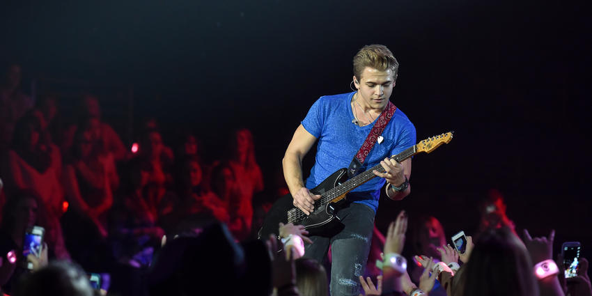 Hunter Hayes plays his guitar on stage for the crowd at the Bryce Jordan Center.