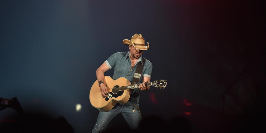 Jason Aldean, playing guitar, wearing his signature cowboy hat and short sleeved western buttoned down western shirt.