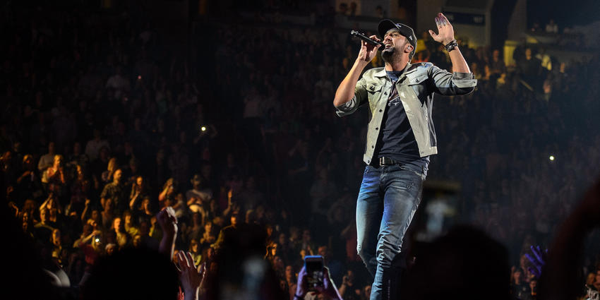 Luke Bryan sings into handheld microphone to a packed crowd during his concert at the BJC.