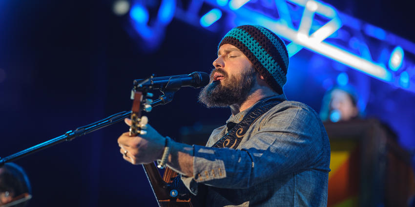 Lead singer, Zac Brown, sings into microphone while playing guitar during the Zac Brown Band performance at the BJC in 2012.