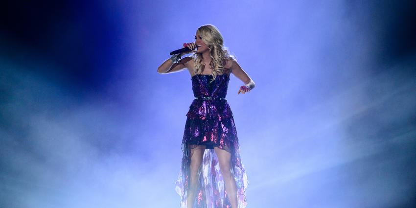 Carrie Underwood sings in front of a purple backlight in the midst of theatrical smoke for the BJC audience in 2012.