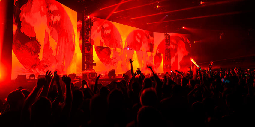 ZEDD waves to the crowd, set up in front of full stage length & height screens displaying red earths.