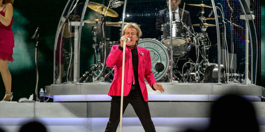 Rod Stewart, wearing a bright pink blazer & tie, sings into a white standing microphone during his concert at the BJC in 2013.