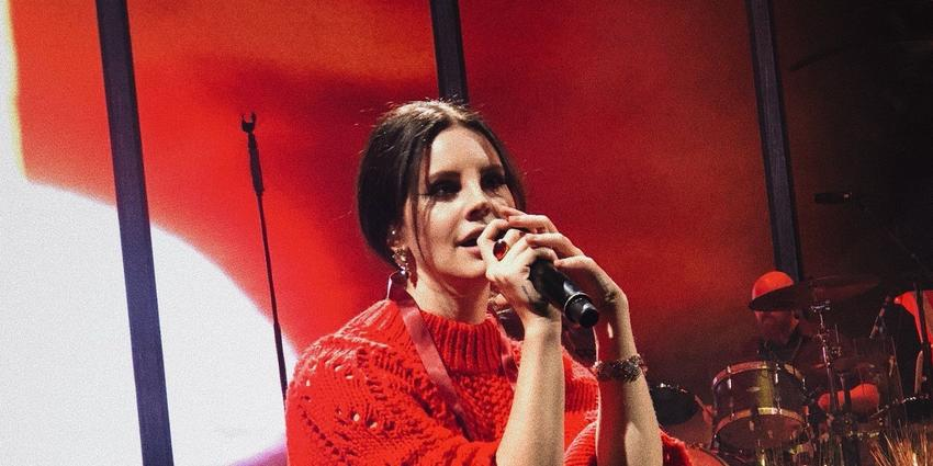 Lana Del Rey sits on stage singing during her performance at BJC