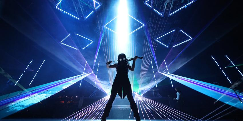 Silhouette of Trans-Siberian Orchestra's violinist performing in front of a mix of blue laser lights at the BJC in 2013.