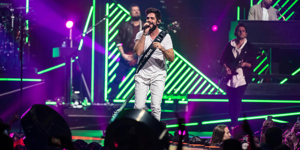 Thomas Rhett singing in to handheld microphone with band and neon green lighting accents in background