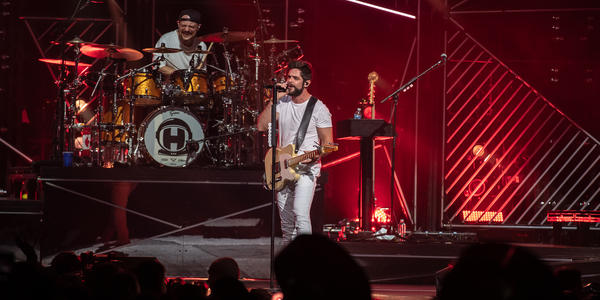 Thomas Rhett holds sings into microphone while playing guitar