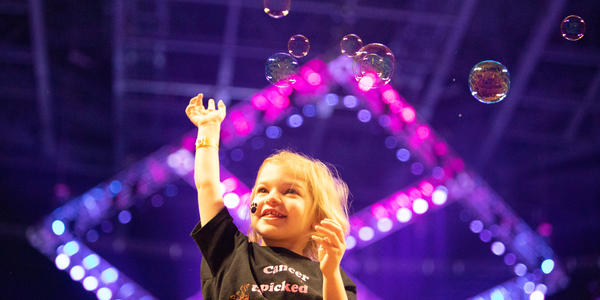 THON child playing with bubbles