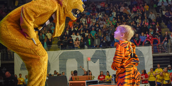 Thon child dressed in tiger costume looks up at PSU Nittany Lion