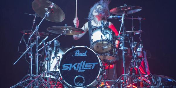 Drummer for the band, Skillet, head bangs and plays during performance at BJC